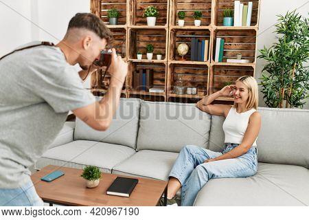 Man making photo to his girlfriend using camera at home.