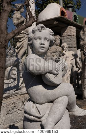 Ancient stone sculpture of naked cherub playing lute in reclamation yard. art and classical style romantic figurative stone sculpture.