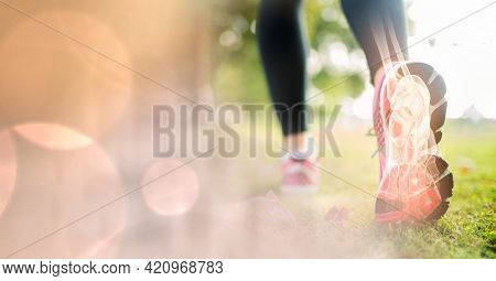 Composition of woman running in park with leg bones visible and spots of light. exercise and injury concept digitally generated image.