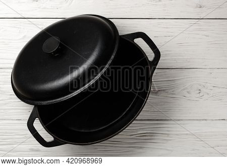 Cast Iron Pot With Lid. A Casserole Pot On A On A White Wooden Background. Empty Clean Castiron Cook