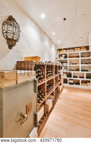 Shelf With Wine Bottles And Retro Vault Located In Brightly Illuminated Cellar Of House