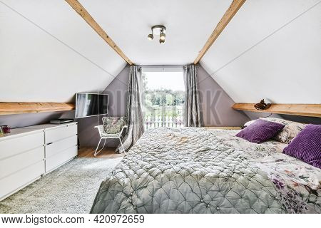 Comfortable Bed With Pillows And Blanket Located Near Chair And Tv Against Window With Curtains In L