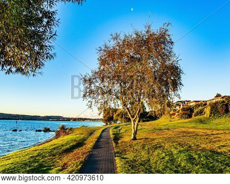 Magnificent sunset. Taupo is the largest lake in New Zealand, North Island. The most popular holiday destinations for tourists. Quiet evening on the lake. Nice walk by the lake