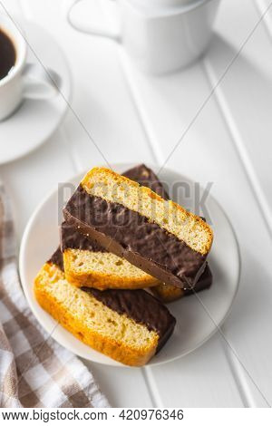 Sliced sponge dessert. Sweet sponge cake with chocolate on white table.