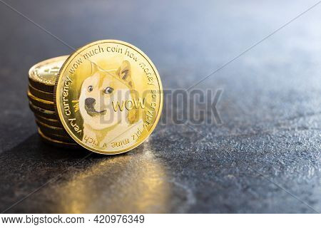 Golden dogecoin coin. Cryptocurrency dogecoin. Doge cryptocurrency on black table.