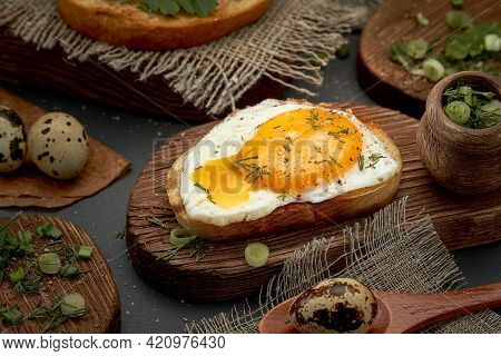 Fried Eggs On A Bun With Black Pepper And Herbs On A Wooden Board. The Scrambled Eggs Are Spreading.