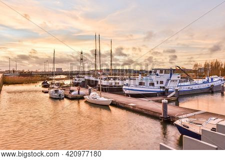 Wharf With Sailboats And Ships Located In Rippling Channel Against Cloudy Sunset Sky In Autumn Eveni