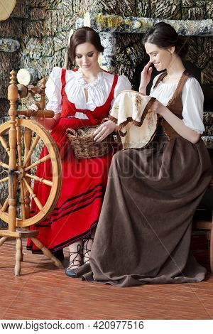 Two Lovely Caucasian Ladies  Posing With Spinning Wheel And Fancywork Hoop In Retro Dress In Rural E