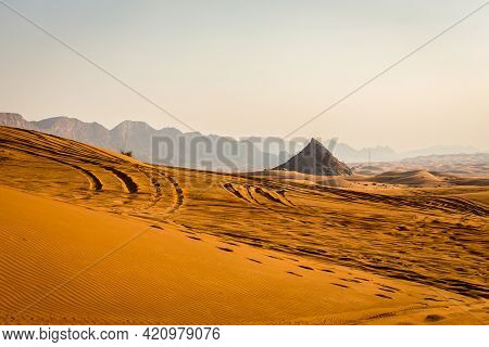 Golden Desert Dunes With Rocky Jebel Al Fayah Mountains In The Background, Footsteps And 4x4 Tire Tr