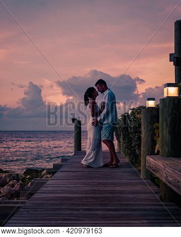 Couple On The Beach Of Curacao During Sunset, Men And Woman Watching Sunset On The Tropical Beach Of