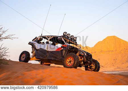 Sharjah, Uae, 16.01.2021. Modern Dune Buggy Parked On Sand In The Desert With Mountains In The Backg