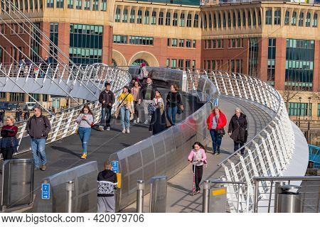 Newcastle, United Kingdom -february 22, 2019: Pedestrians Stroll On The Gateshead Millennium Bridge