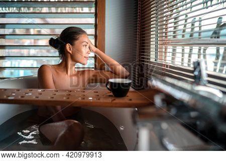 Luxury bath Asian woman relaxing in warm water enjoying view from bathroom window lying in bathtub with bath wooden board caddy drinking coffee cup.