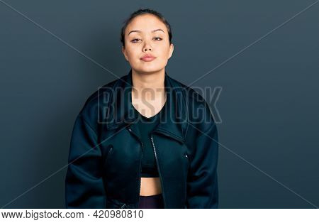 Young hispanic girl wearing sportswear looking sleepy and tired, exhausted for fatigue and hangover, lazy eyes in the morning.