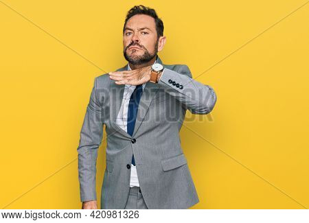 Middle age man wearing business clothes cutting throat with hand as knife, threaten aggression with furious violence