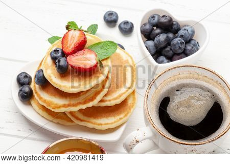Healthy breakfast with pancakes. Homemade american pancakes with berries and honey