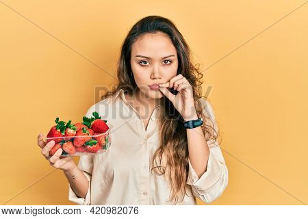 Young hispanic girl holding strawberries mouth and lips shut as zip with fingers. secret and silent, taboo talking