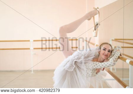 Beautiful Young Ballerina Is Rehearsing A Solo Part In A Class With A Barre. Slender Graceful Dancer