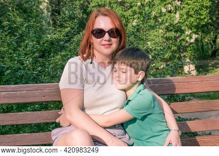 Young Woman With Red Hair And Boy Are Sitting In Park On Bench. The Son Hugs His Mother Gently. Happ