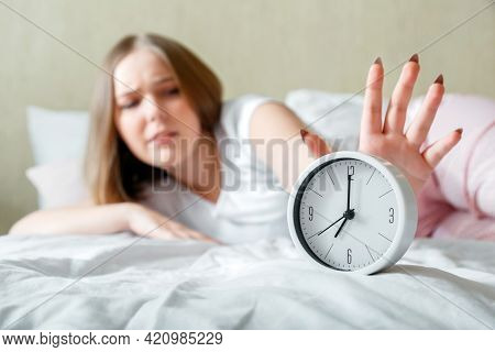 Overslept Young Woman Awake In Pajamas Turns Off Alarm Clock In Hurry. Morning Routine And Wake Up L