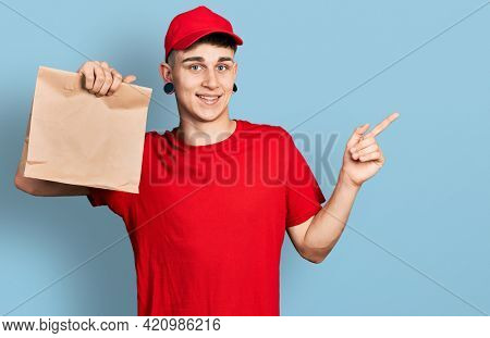 Young caucasian boy with ears dilation holding take away paper bag smiling happy pointing with hand and finger to the side