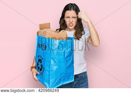 Young beautiful woman holding recycling wastebasket with paper and cardboard annoyed and frustrated shouting with anger, yelling crazy with anger and hand raised