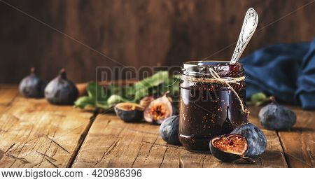 Red Fig Jam In Jar With Fresh Blue Figs. Homemade Preparations And Canning. Rustic Wooden Table Back