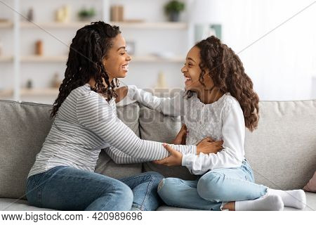 Happy African American Mom Tickling Her Laughing Girl Kid
