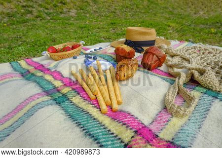 Still Life With Breadsticks, Strawberries, Straw Hat, And Pastry On Checkered Plaid Cross Green Gras