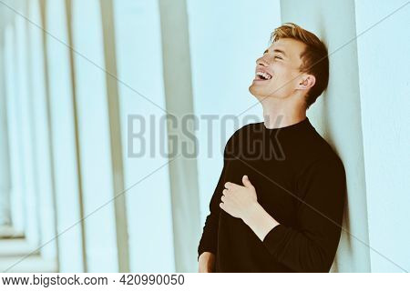 Happy young man in black pullover stands next to white columns in the old town and laughs. Happy life, happy people concept.
