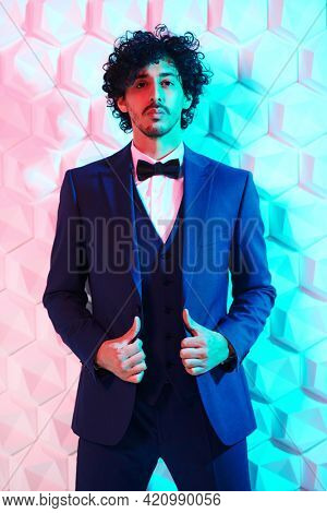 Men's fashion. Portrait of a brunet handsome man in elegant three-piece suit and a bow-tie posing at studio in mixed color light.