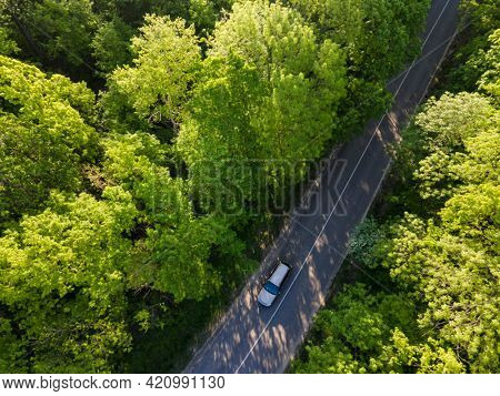 Car on road in the forest in summer time nature from air . View from a drone. Aerial view.