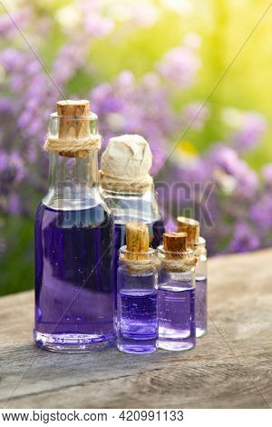 Glass bottle of Lavender essential oil on wood table and flowers field. Lavendula oleum
