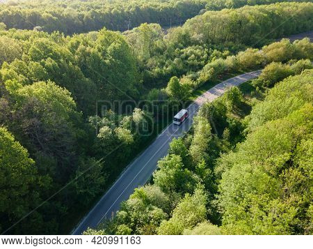 white bus on Road in beautiful summer forest aerial.