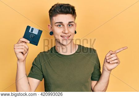 Young caucasian boy with ears dilation holding floppy disk smiling happy pointing with hand and finger to the side