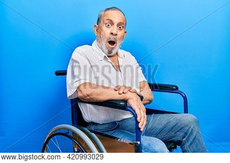 Handsome senior man with beard sitting on wheelchair in shock face, looking skeptical and sarcastic, surprised with open mouth