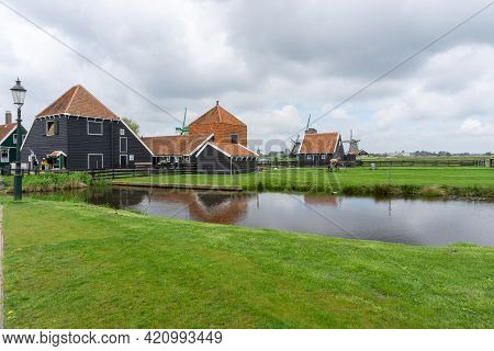 View Of Traditional 18Th-century Dutch Farmhouses And Windmills In North Holland Province