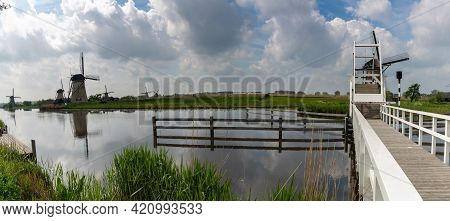 Panorama View Of Picturesque Wooden Draw Bridge And Windmills On The Canals Of South Holland