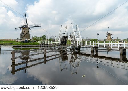 Picturesque Wooden Draw Bridge And Windmills On The Canals Of South Holland