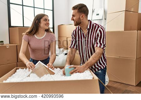 Young caucasian couple smiling happy unboxing cardboard box at new home.