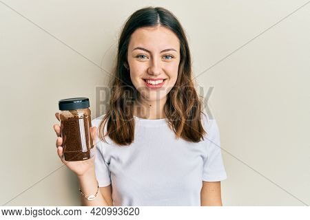 Young brunette woman holding soluble coffee looking positive and happy standing and smiling with a confident smile showing teeth