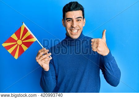 Handsome hispanic man holding macedonian flag smiling happy and positive, thumb up doing excellent and approval sign