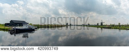 Panorama View Of The Windmills And Canals Of Kinderdijk In South Holland With A Dock And Boat In The