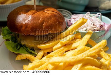 A Selective Focus View Of A Delcious Homemade Cheeseburger With French Fries And Cole Slaw