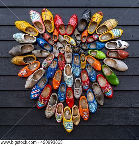 A Close Up View Of Many Colorful Traditional Clogs Hanging On The Wall Of A House In The Netherlands