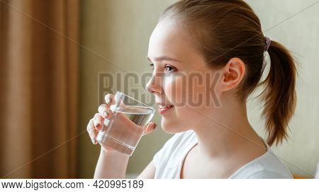 Smile Young Woman Drinks Glass Of Pure Water In Morning After Waking Up. Happy Teen Girl Maintains W