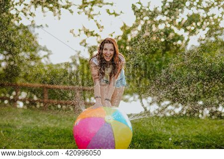 Pretty Young Woman In Jeans Summer Shorts Playing With Water Splashing Ball On Green Glade. Happines