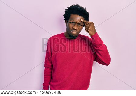 Young african american man wearing casual clothes pointing unhappy to pimple on forehead, ugly infection of blackhead. acne and skin problem