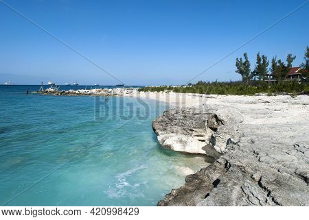 The View Of Eroded Rocky Grand Bahama Coastline And Industrial Ships In A Background.