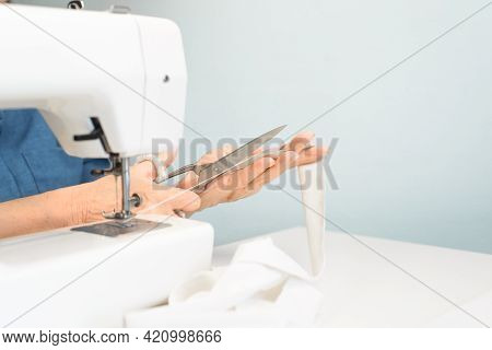 Woman Working On A Sewing Machine At Home. Senior Dressmaker's Hands Cutting Thread, Close-up.hobby